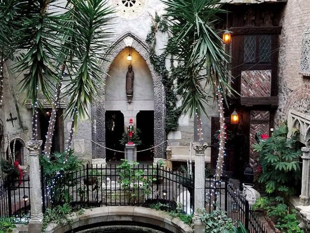 Photo of the cloister courtyard decorated for the holidays with strings of lights and touches of red amid the greenery