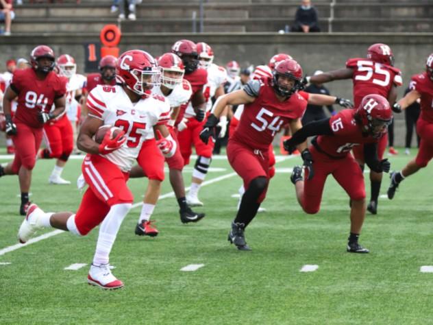 Harvard senior linebacker Jack McGowan (54) and sophomore safety Victor Tademy chase down Cornell runner SK Howard.