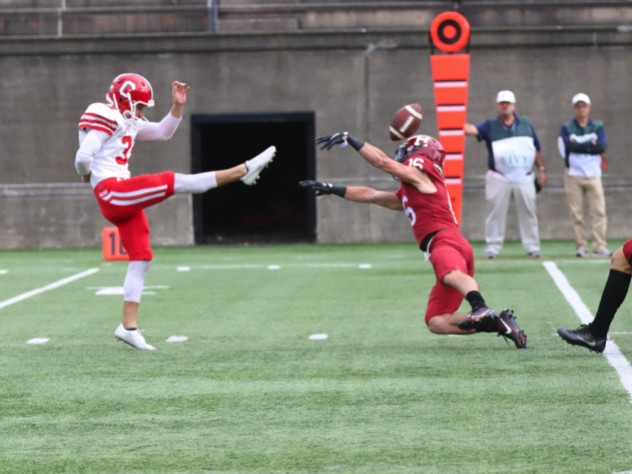 Harvard junior safety James Herring gets a hand on the punt of Cornell's Koby Kiefer.