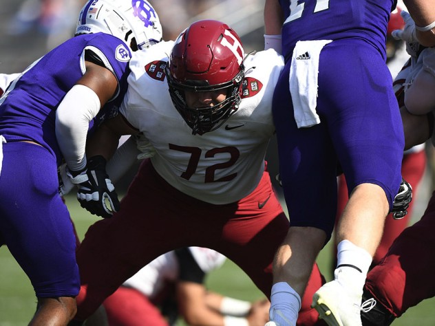 A Harvard lineman holds back two Holy Cross defenders
