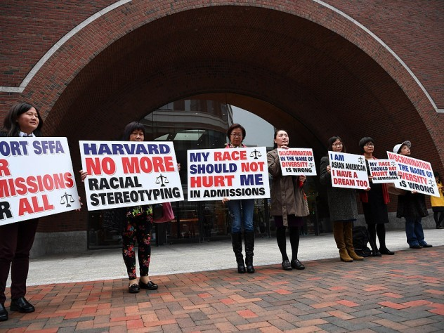 """Photograph of demonstrators in front of the federal courthouse in Boston where the SFFA v. Harvard trial took place, with signs reading """"Harvard No More Racial Stereotyping"""" and """"My Race Should Not Hurt Me In Admissions."""