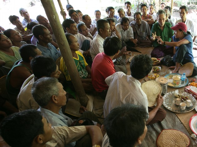 Debbie Aung Din Taylor (with red hat), co-founder of Proximity Designs, meets with villagers in A Phaung Gyi, in Dedaye township in the Ayeyarwaddy River Delta. Many of the villagers use crop loans provided by Proximity Designs to plant rice. It also provides agricultural advice, and now distributes a line of popular, low-cost solar lights (90 percent of Myanmar's rural households are not on an electrical grid).
