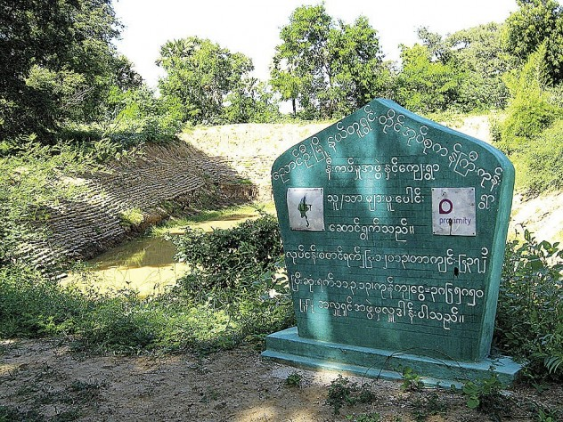 "Hundreds of miles north of the delta, farmers in Myanmar's Dry Zone, like these in Kangyikone village, grow peanuts as a cash crop—and rely on oxen for power. Proximity advisers are introducing practices like ""green manure"" plantings to enrich the soil. The sign details an infrastructure-aid project, managed by Proximity, to restore the village's drinking-water pond."