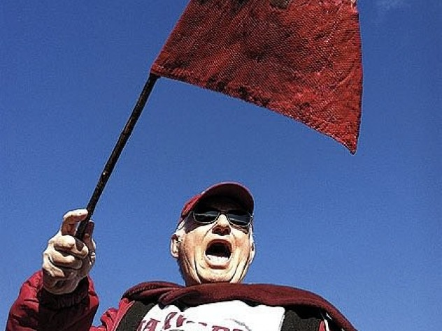 "Bill Markus '60 waving the Little Red Flag at Yale Bowl (see <a href=""http://harvardmagazine.com/2003/09/superfan.html"">""Superfan""</a>). Crimson loyalists have taken the flag to 124 Yale games since 1884; on Markus's watch, Harvard is now 12-1."