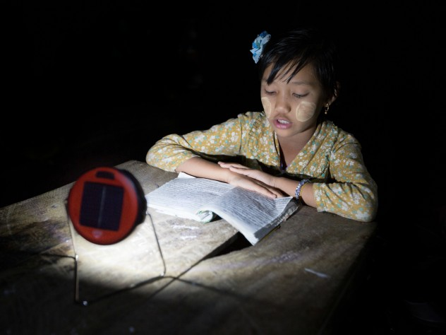 enabling reading, or homework, at night, in lieu of candles, which are expensive, a fire hazard in bamboo houses, and unsuitable for use under mosquito netting. (The white paste on the girl's cheeks is <i>thanaka,</i> a cosmetic paste made from ground bark, which many women and girls in Myanmar apply to guard against sunburn and to protect the skin.)