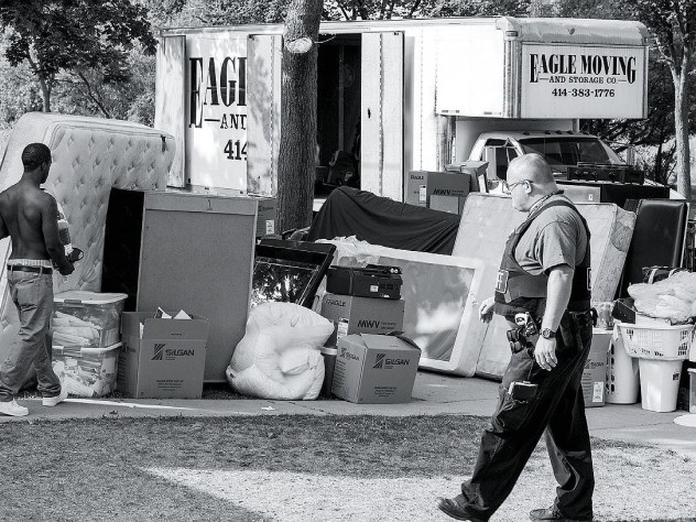 A deputy sheriff supervises as an evicted tenant carries belongings to the curb.