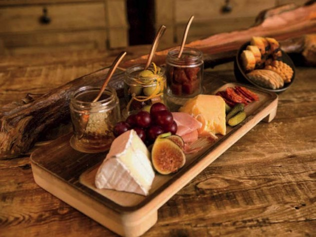 A platter of cheese, cured meats, and fruit
