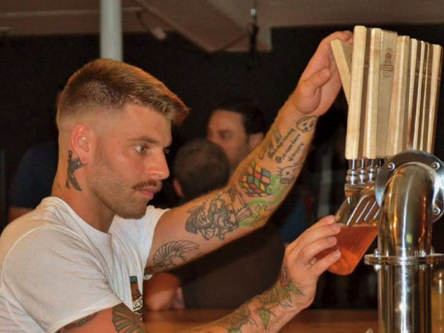 Handsome, tattooed bartender at Provincetown Brewing Company tapping craft beer for a customer
