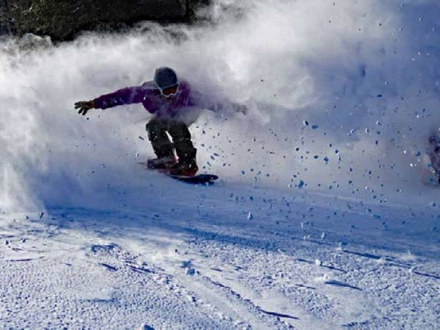 Skier coasting down the mountain with snow sprays