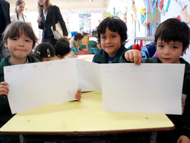 Children in a UBC classroom display a writing exercise on which they've been working.