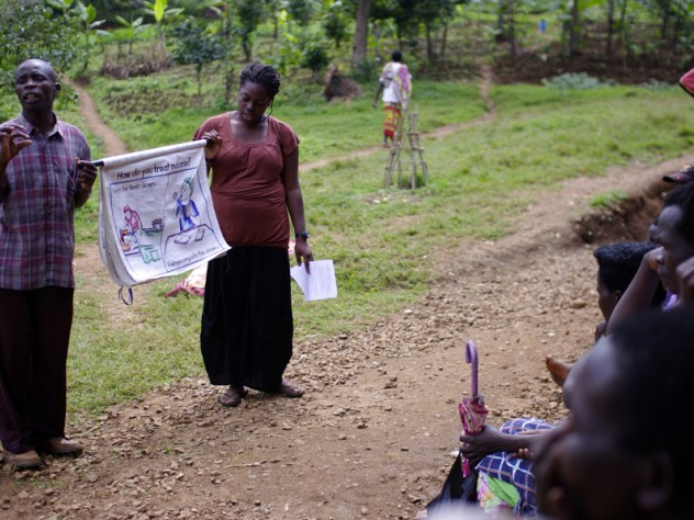 Kiahana Brooks '10 (right) teaches about malaria prevention and treatment to patients waiting to be seen at the clinic. Clinic worker Richard Kimanayi, left, translates.