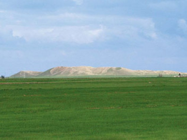 The high central mound of Tell Brak, formed by generations of mud structures built on top of one another, rises out of the alluvial plain.