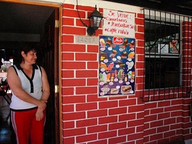 Herrera stands in the doorway of her home.