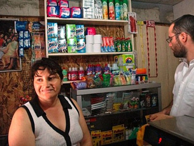 """Marta Herrera (pictured here with Gonzalo Arteaga) has set up a small convenience store in the front room of her house at the ELEMENTAL development in Lo Espejo. Herrera, who lives here with her husband and two children, says she was unemployed before. """"I prefer this,"""" she says. """"My life is so happy now."""""""