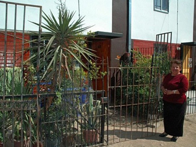 Ortega stands in front of her home. She fenced in her yard and filled it with plants, which she sells to support herself and her two-year-old grandson.