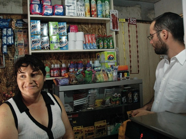 Marta Herrera, pictured with ELEMENTAL project manager Gonzalo Arteaga, has set up a small convenience store in the front room of her house at the Lo Espejo development.