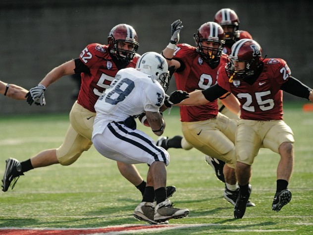 HOT PURSUIT: Defenders Schultz (52), Curtis (91), and Barnes (25) closing in on Yale back Mike McLeod.