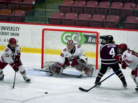 Photograph of several players competing for the puck in front of the Harvard goal