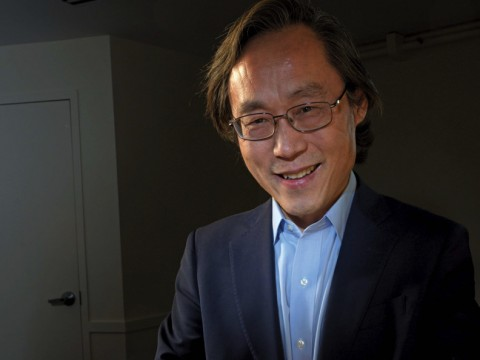 Frank Hu holds a plate filled with food.