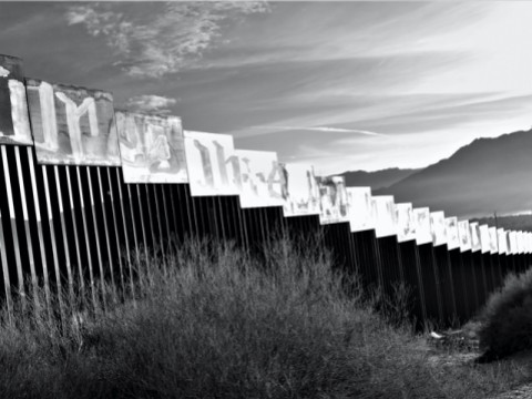A photograph of the border wall stretching toward a mountain in the distance