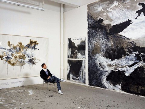 Artist Shen Wei in his studio amid his large-scale abstract paintings
