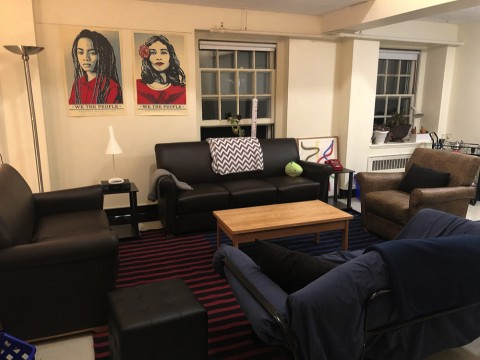 Photograph of the author's Harvard dorm room with chairs, sofa, posters