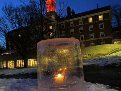 "Close-up image of an ""ice lantern"" (a light set in an ice casing) in the snow on Radcliffe Quad"