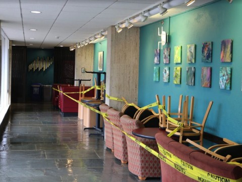 A hallway in Quincy House, with chairs cordoned off limits against the wall