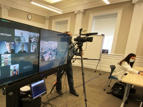 A hybrid classroom showing the large screens enabling a teacher to see all the students, remote or present, as he is followed by a camera operator.