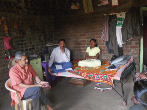Photograph of Vikram Patel visiting with family members of a farmer in Maharashtra, India, who committed suicide