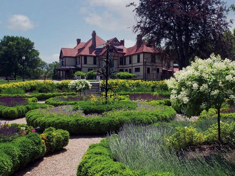 Wide view of formal gardens with a historic mansion in the background