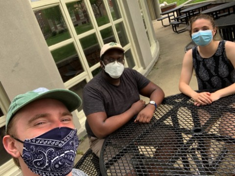 Photo of the author sitting with two friends, all in masks, in the Radcliffe Quadrangle as they watched virtual Commencement