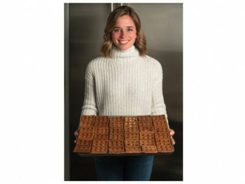 A woman holds a tray of waffles