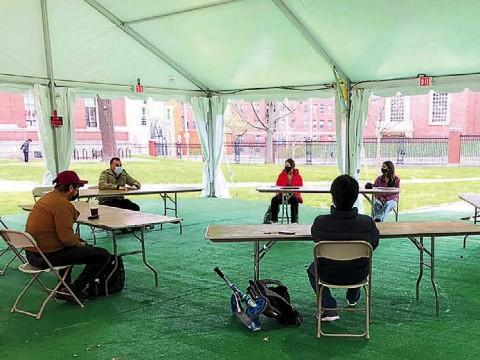 Photograph of teaching a playwriting class under a tent outdoors