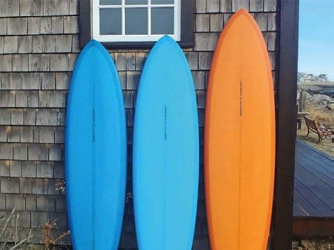 Two blue surfboards and an orange on rest on end against a weatherbeaten wall.