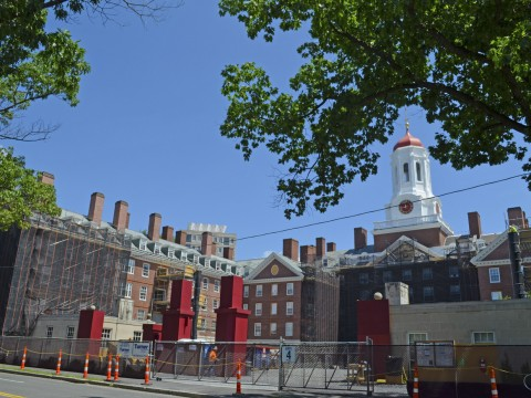 View of Dunster House, the first residence for upperclassmen to undergo full renewal, from Memorial Drive. Seven weeks after the reconstruction project began, Dunster is almost completely scaffolded, and its iron gate has been removed.