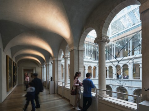 A few visitors in the arcade overlooking the Calderwood Courtyard of the Harvard Art Museums