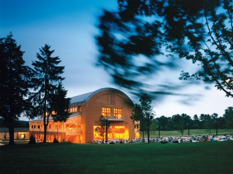 """Seiji Ozawa Hall at Tanglewood, the summer home of the Boston Symphony Orchestra, in Lenox, Massachusetts. The hall opened in 1994. With the """"barn door"""" open, picnickers enjoy a concert."""