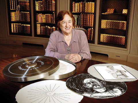 "Porter University Professor Helen Vendler in Houghton Library with a copy of the Arion Press edition of John Ashbery's ""Self-Portrait in a Convex Mirror"""