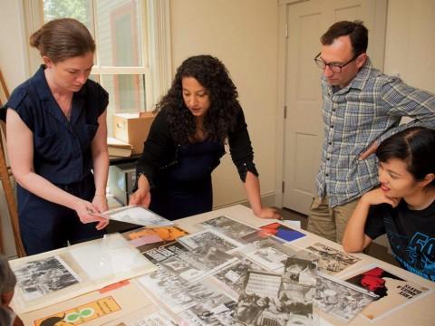 Hinton arranges materials for the Angela Davis exhibit with (from left) Radcliffe arts program manager Meg Rotzel, gallery coordinator Joe Zane, and Pforzheimer fellow Jackie Wang.