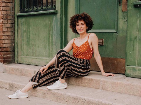 Adriana Colón, a casually dressed, smiling young woman with curly brown hair, sits in a doorway.