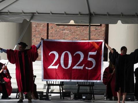 Danoff Dean of Harvard College Rakesh Khurana and Harvard Alumni Association president Vanessa Liu '96, J.D '03 unfurl the class of 2025 banner