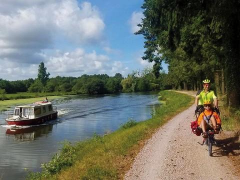 Michael Lyon and son ride a bike next to a river.