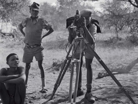 """""""/Gaishay focusing the camera,"""" a photograph taken during a 1957-58 ethnographic expedition in Namibia, shows three indigenous boys, one standing behind a camera on a tripod"""