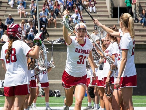 Photograph of Harvard women lacrosse players celebrating.
