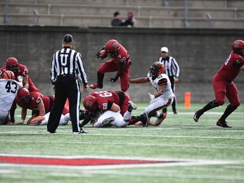 Harvard running back Aaron Shampklin hops over a Harvard teammate with a football in hand.
