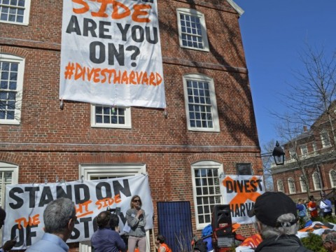 Divest Harvard signs hangs from Mass. Hall.