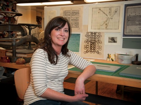 Hulsey in her studio, with letterpress machines behind her