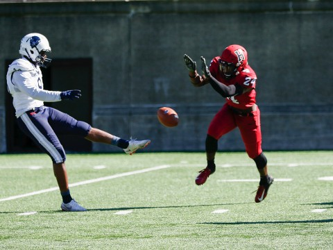 Harvard freshman Khalil Dawsey blocks the punt of Howard's Isaiah Moore.