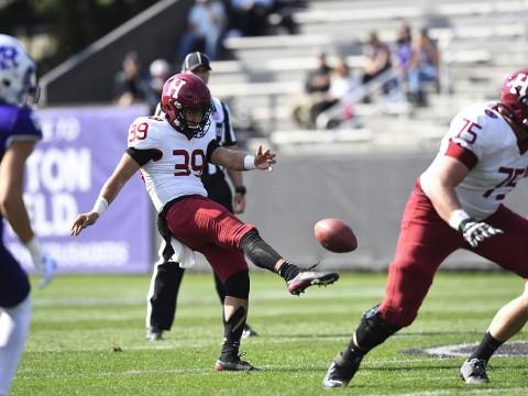 The Harvard punter kicks the football